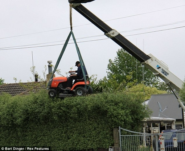 Riding Mower and Crane Trims Hedges
